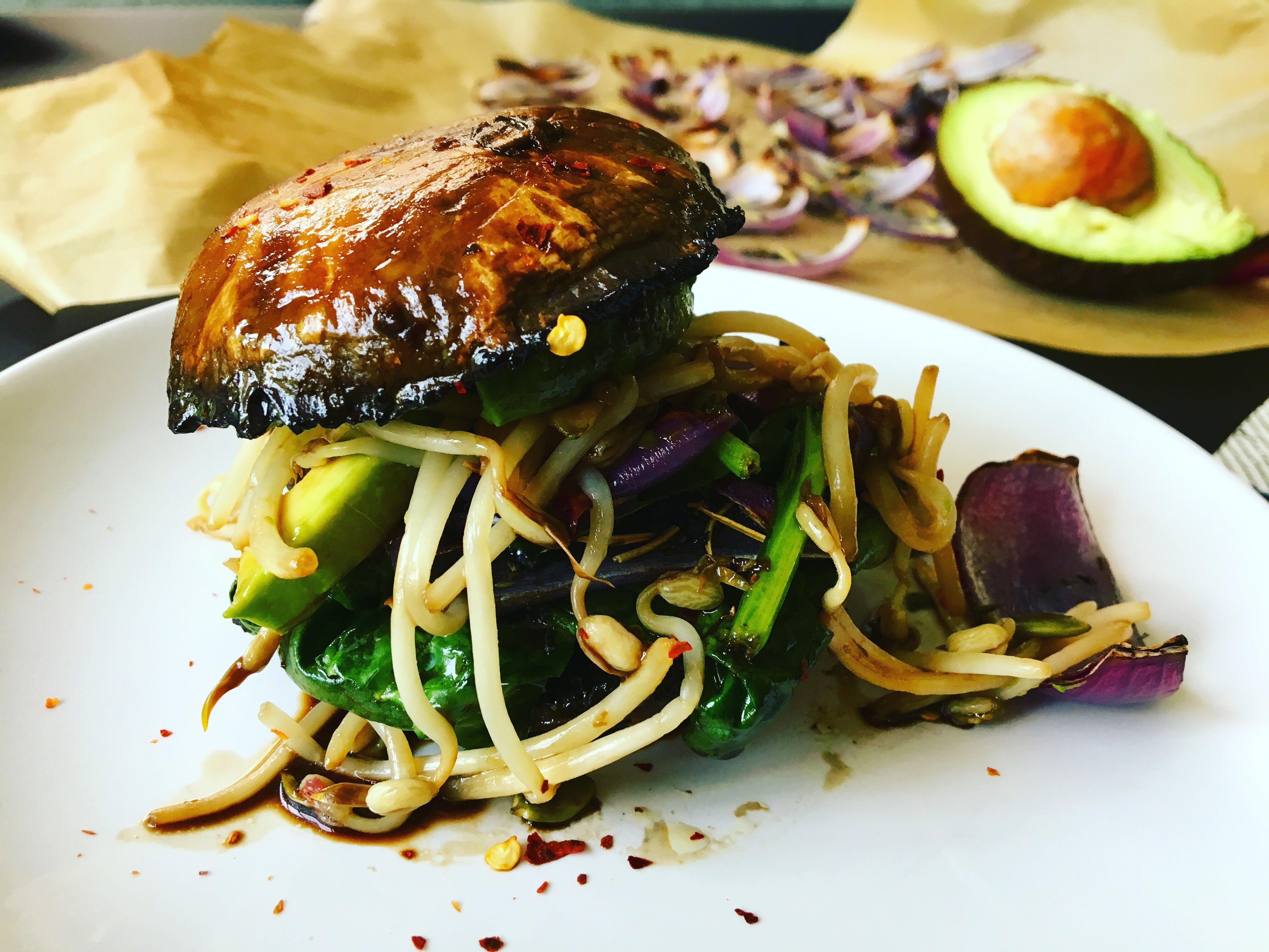 Burger portobello avec pousses de soja, avocat, oignons rouges rôtis au four, sauce balsamique tamari